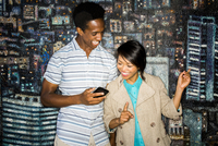 Couple using cell phone by mural