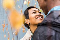 Close up of smiling couple standing in autumn leaves