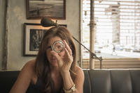 Caucasian woman looking through empty glass in cafe