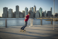 Caucasian skateboarder doing trick at waterfront, New York, United States