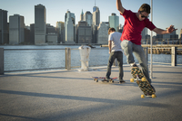 Caucasian skateboarders doing tricks at waterfront, New York, United States