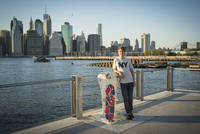 Caucasian skateboarder smiling at waterfront, New York, United States