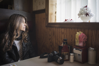 Caucasian woman sitting in diner booth near window