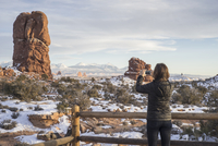 Caucasian woman photographing rock formations in landscape
