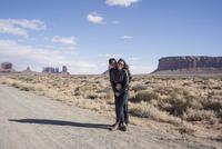 Caucasian couple hugging on desert dirt road