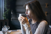 Caucasian woman drinking coffee in cafe