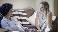 Caucasian lesbian couple talking on sofa