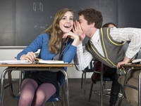 Students whispering at desks in classroom