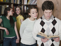 Students reading book in library
