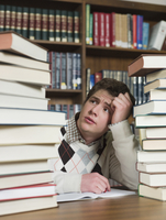 Student staring at stacks of books in library