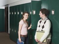 Students talking at locker in school hallway