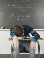 Student sleeping at desk in classroom