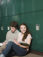 Students sitting at locker in school hallway