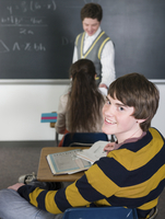 Student smiling at desk in classroom