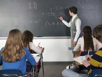 Teacher writing on chalkboard in classroom
