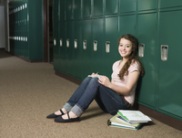 Mixed race student sitting at locker in school hallway
