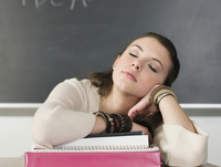 Bored student sleeping at desk in classroom
