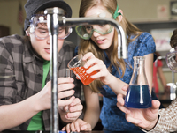 Students performing experiment in science lab classroom