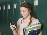 Mixed race student using cell phone by locker in school hallway