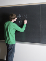 Student writing on chalkboard in classroom