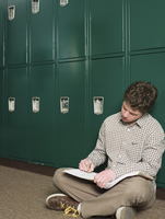 Student writing notes at locker in school hallway