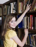 Student choosing book in library