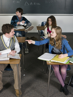 Students talking at desks in classroom