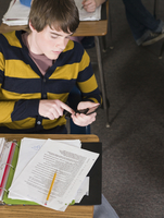Student using cell phone at desk in classroom