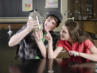 Students examining frog in science lab classroom