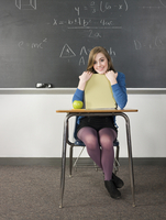 Student holding book at desk in classroom