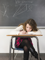 Student writing notes at desk in classroom