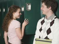 Students talking at lockers in school hallway