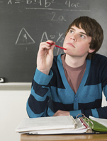 Student thinking at desk in classroom