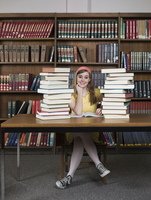 Student sitting with books in library