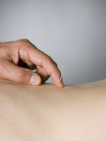 Close up of acupuncturist checking needle in back of patient