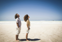 Couple standing in wind on beach