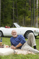 Older man laying on picnic blanket in park