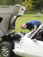 Older man examining broken-down convertible in park