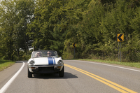 Older couple driving convertible on rural road