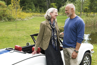 Older couple standing by convertible