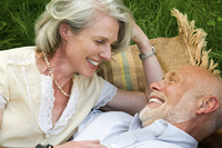 Older couple laying on picnic blanket