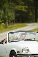 Older couple kissing in convertible on dirt road