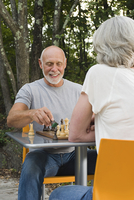 Older couple playing chess in backyard