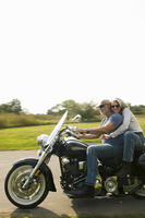 Older couple riding motorcycle on rural road