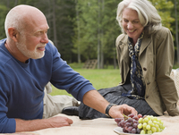 Older couple eating grapes at picnic in park