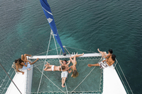 High angle view of friends sunbathing on sailboat
