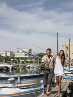 Couple walking on wooden dock in urban harbor