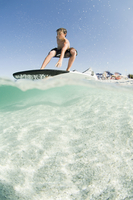 Low angle view of man standing on surfboard