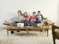 Friends relaxing on sofa in living room
