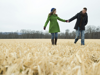 Caucasian couple holding hands in rural field